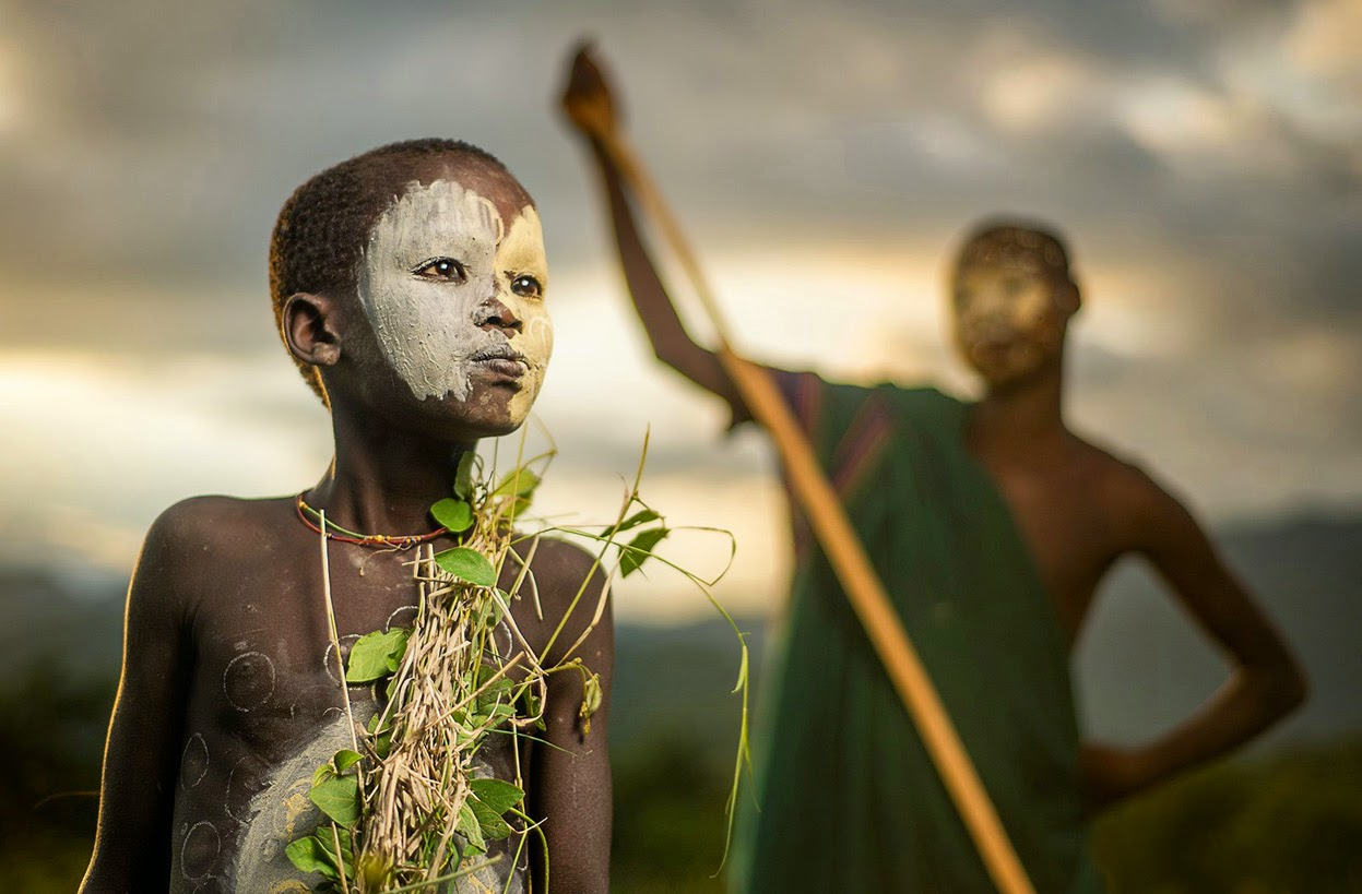 A BOY OF THE NOMADIC SURI TRIBE OF ETHIOPIA, IN TRADITIONAL FACE/BODY PAINT AND ATTIRE - 29 Breathtaking Photographs of The Human Race