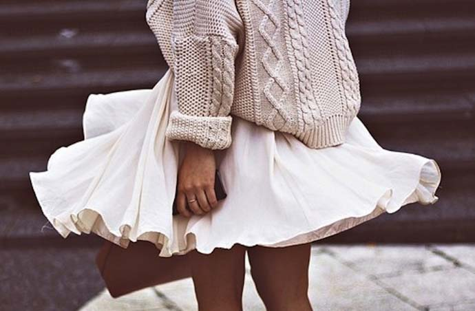 Cream colored chunky knitted sweater and a lightweight short white skirt