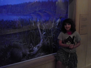 girl withe cane in front of a case with a raccoon.