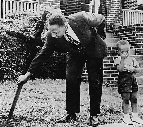 25 Breathtaking Photos From The Past - Martin Luther King Jr removing a burned cross from his front yard with his son at his side. Atlanta Ga 1960