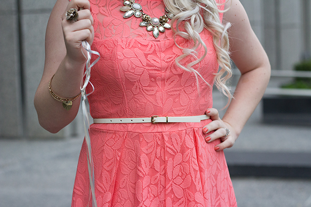 White skinny leather belt over a coral lace dress.