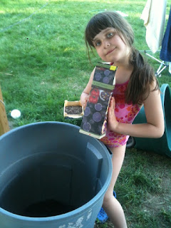 Little girl posing with bag of seed potatoes and the garbage can.