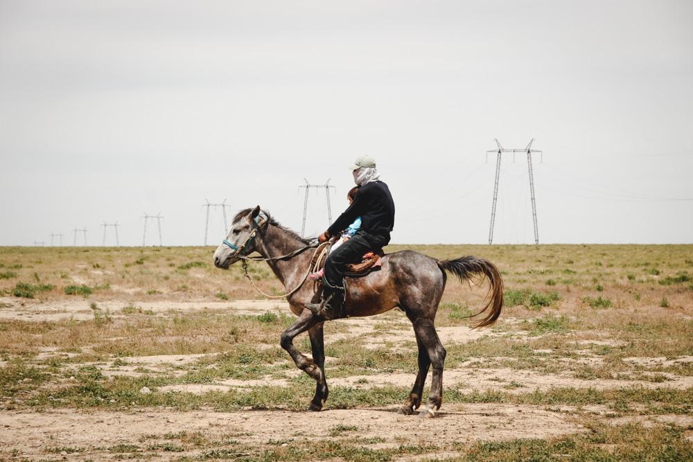 Mann auf Pferd in kasachischer Steppe