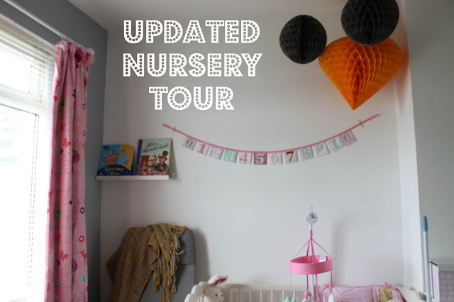 grey yellow and pink themed nursery with 0-10 pink bunting and grey and yellow paper balls hanging from ceiling