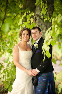 bride and groom standing under a tree after getting married wearing a silk gown and jenny packham headband