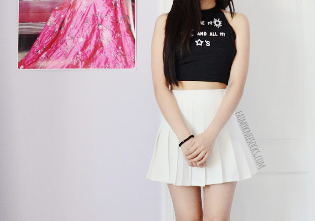 A Tumblr-inspired monochromatic outfit featuring Dresslink's halter tie-back crop top and a white pleated American Apparel tennis skirt.