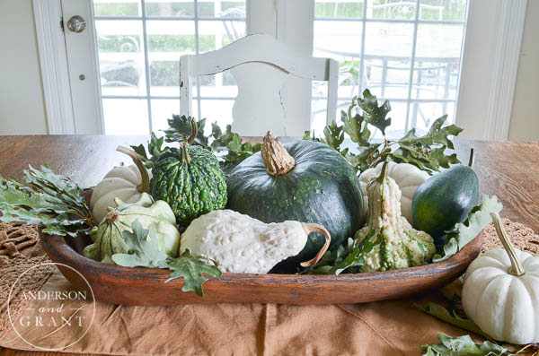 An inexpensive and easy way to create a beautiful fall centerpiece is to look to nature.  Fill a dough bowl with pumpkins, squash, gourds, and leaves.  Find out more at www.andersonandgrant.com.