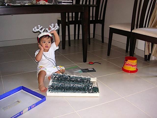 Kecil in reinderr headband, playing with the Christmas lights