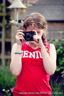 Girl looking through view finder of camera