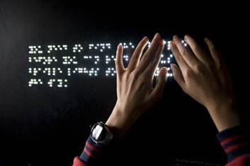 L.E.D. illuminated braille, with hands running over it.