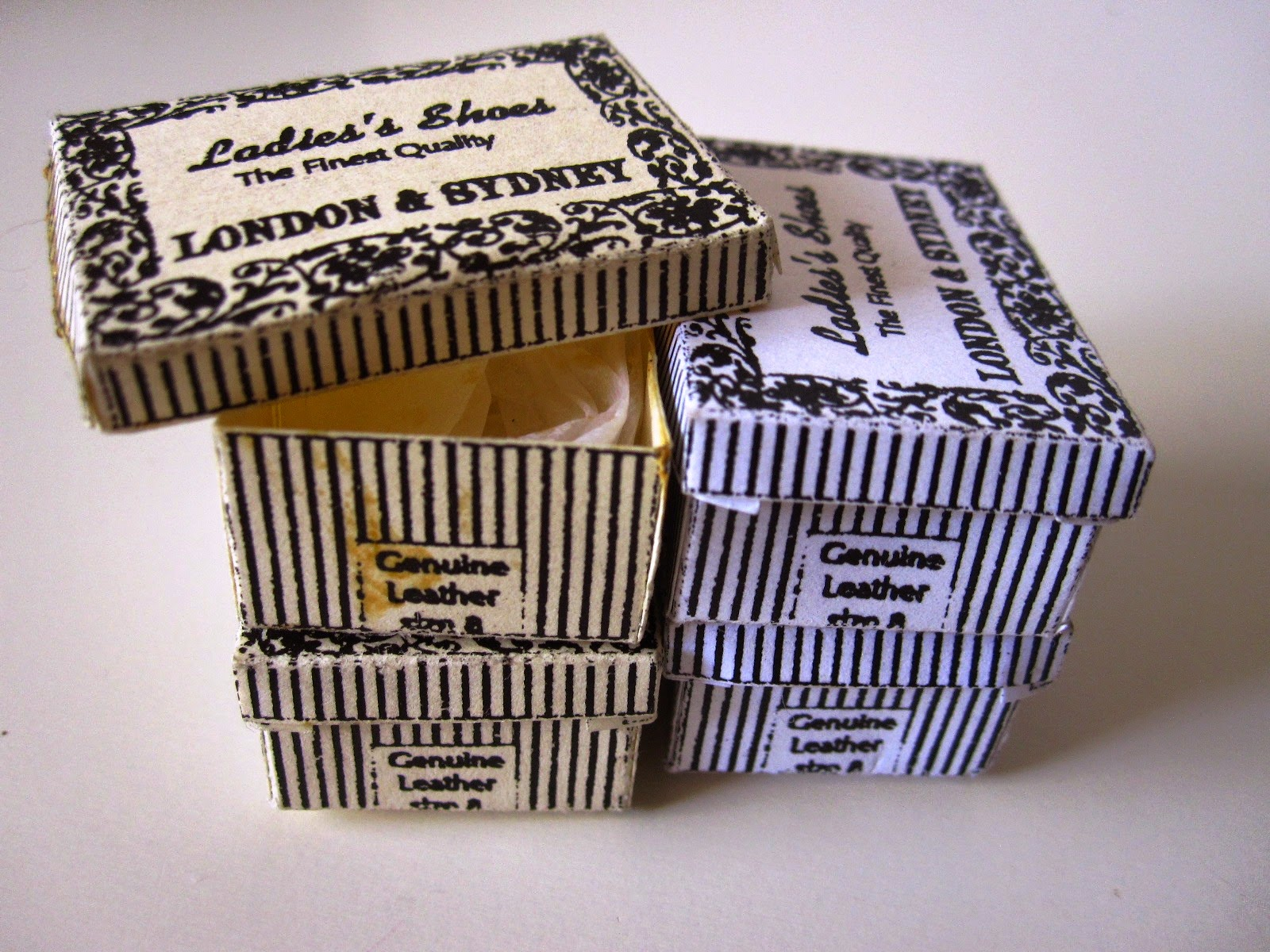 Collection of four miniature vintage black and white striped shoe boxes.