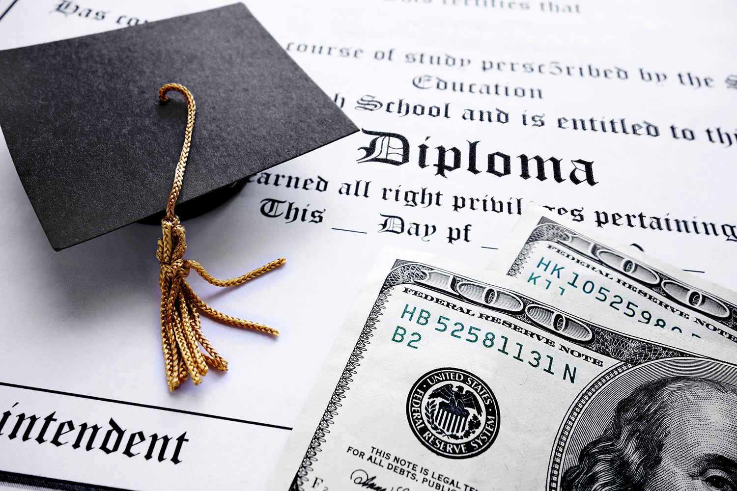 stock photo image: graduation cap and dollars lay on a diploma