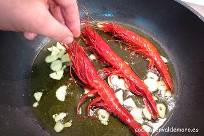 Echando los carabineros a la sartén con los ajos laminados