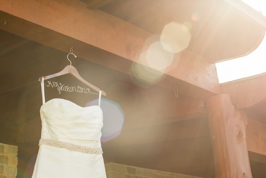 brides dress hanging in the sunshine on hanger with her new last name