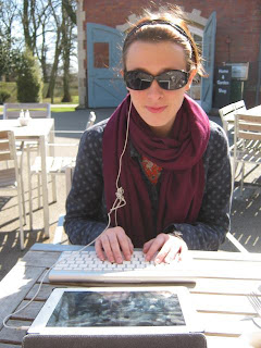 A picture of Imi writing in the sun on an iPad with a headphone in her ear.