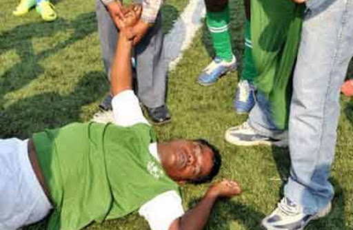 Indian footballer D Venkatesh lays on the pitch after collapsing during a match