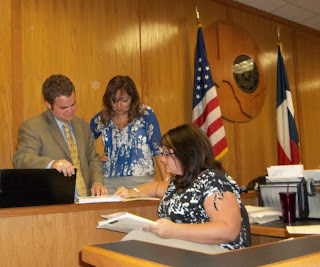 Intern Logan Lane (l)confers with Legal Assistants Iris Cheshire (center) and SHSU Alumna Kasey Wickel ('07) in an Austin County courtroom.