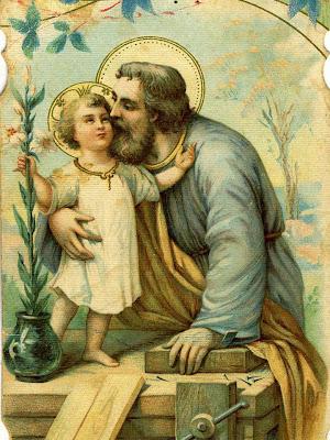 En la omagen San Jose besa al Niño Jesus que esta sobre su mesa de carpintero
