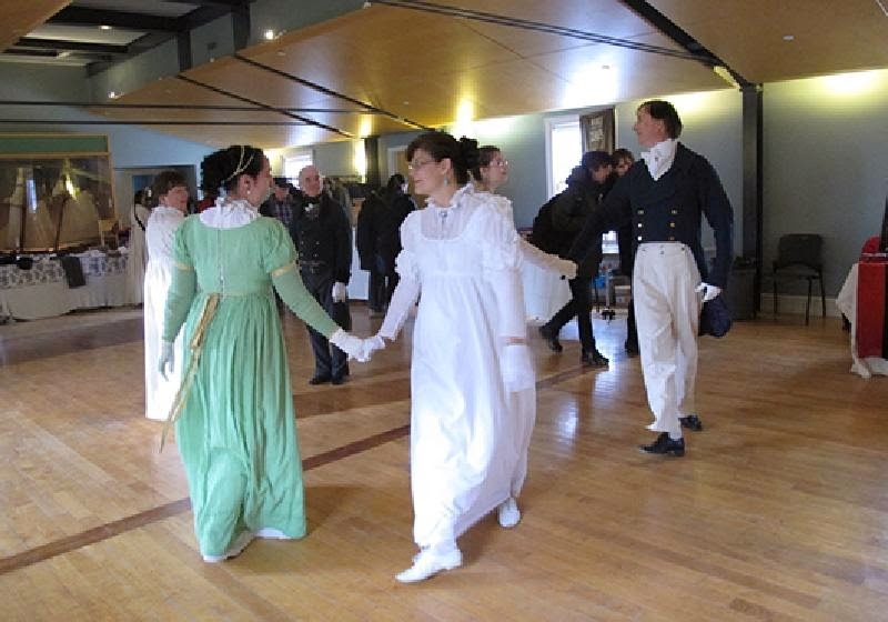 A group of people dancing in historic costumes