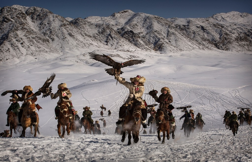 70 Of The Most Touching Photos Taken In 2015 - Chinese Kazakh eagle hunters ride with their eagles during a local festival.