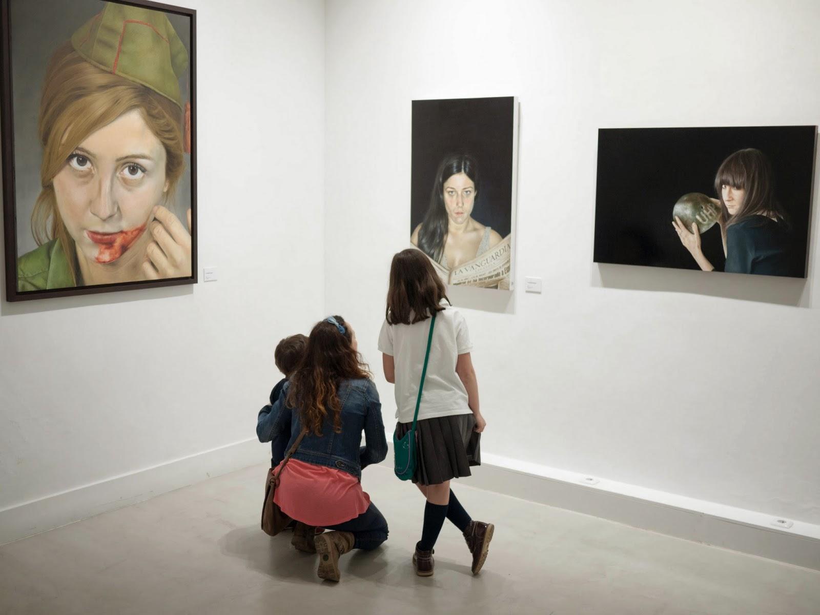 Mujer con dos niños mirando cuadros de exposición de pintura