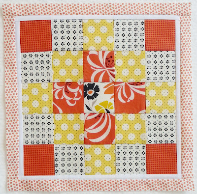 Patchwork quilt block with an orange and yellow color scheme