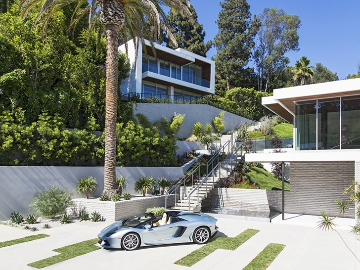Sport car parked in front of Sunset Plaza Drive modern mansion in Los Angeles