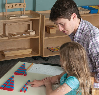 NAMC montessori teacher helps girl with math materials montessori prepared environment class decor