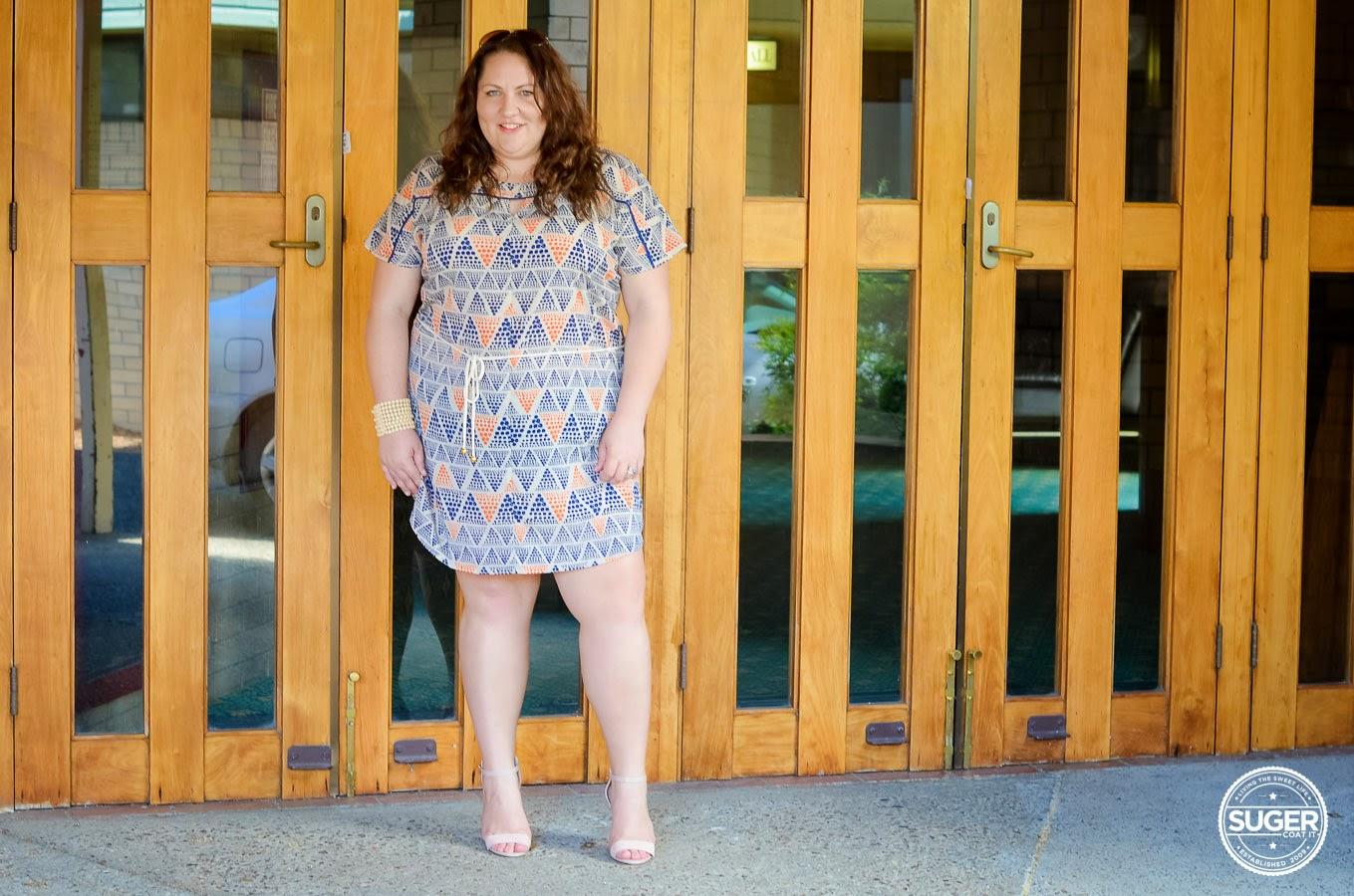 Melissa from Suger Coat It blog wearing orange and blue print short dress