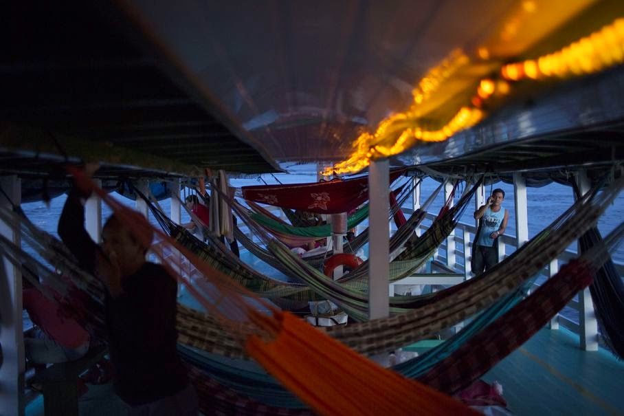 "In this May 22, 2014, photo, hammocks hang in the ""Almirante Barbosa"" regional boat, as it travels on the Solimoes river near Manaus, Brazil. Travelers without hammocks will have a hard time finding a place to sit on the boat, and competition for on-board real estate can be fierce. On the often-overcrowded ships, hammocks are hung from the overhead wooden beams and stacked two- or even three-high bunk bed-style, with adults on the lower levels and kids above."