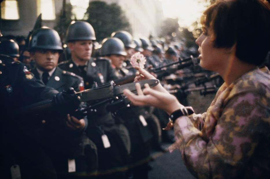 17 year old Jan Rose Kasmir offers a flower to soldiers during the Pentagon anti-war protest in 1967. - The 63 Most Powerful Photos Ever Taken That Perfectly Capture The Human Experience