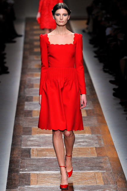 model from valentino fall 2012 runway show wearing a red dress with scalloped hemline and neckline 