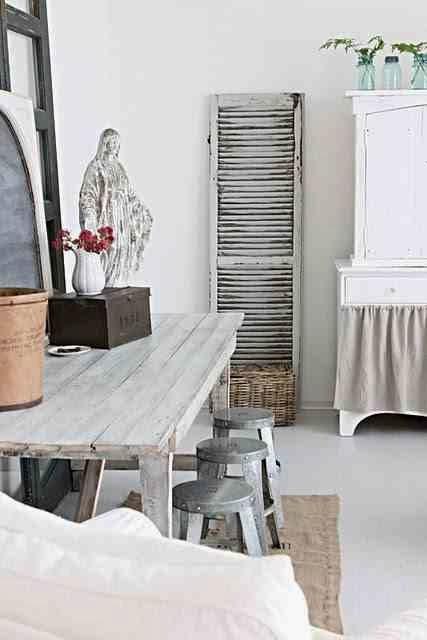Ocynkowane taborety, rustykalne wnętrze, drewniany biały stół,  biała podłoga, białe wnętrzre