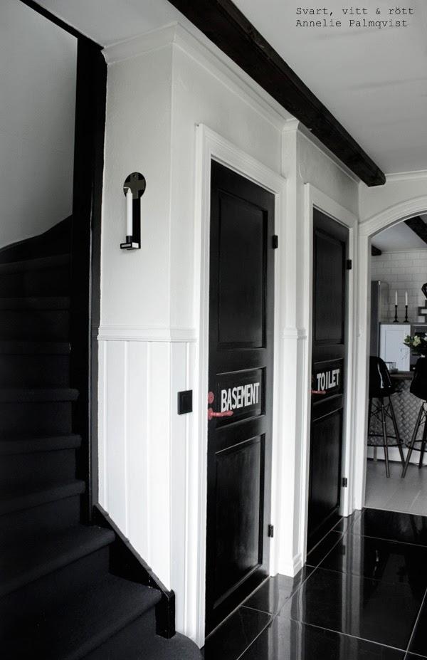 lampett kristina stark, hall, svartvitt, svartvit hall, svart klinkers, vita väggar, svart trappa, trappa med svart matta, svarta kontakter, svartmålade dörrar, vit text, takbjälkar,