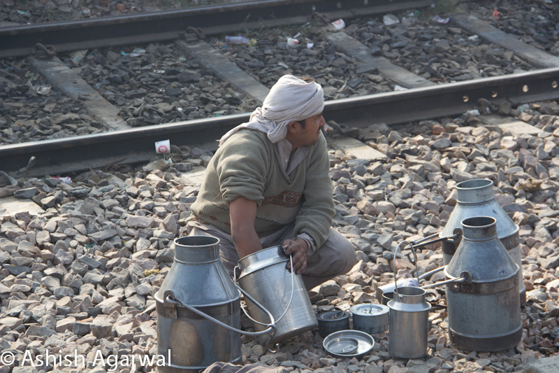 Milk vendors doing some kind of work on the utensils between the train tracks