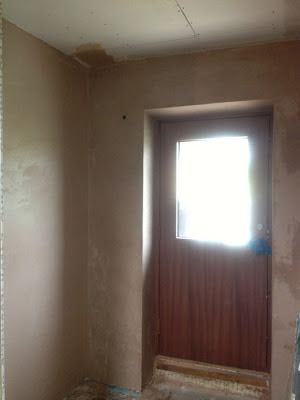 Plasterboard by front entrance plastered over and looking neat