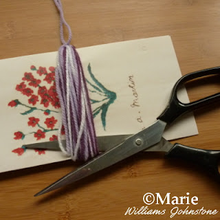 Using scissors to cut the yarn strands
