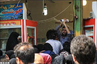 پاشیدن آب بر روی شهروندان متقاضی مرغ دولتی برای جلوگیری از ازدحام