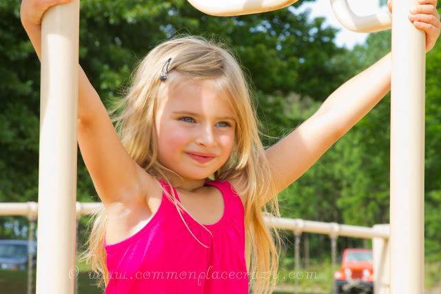 Smiling little girl on playground equipment