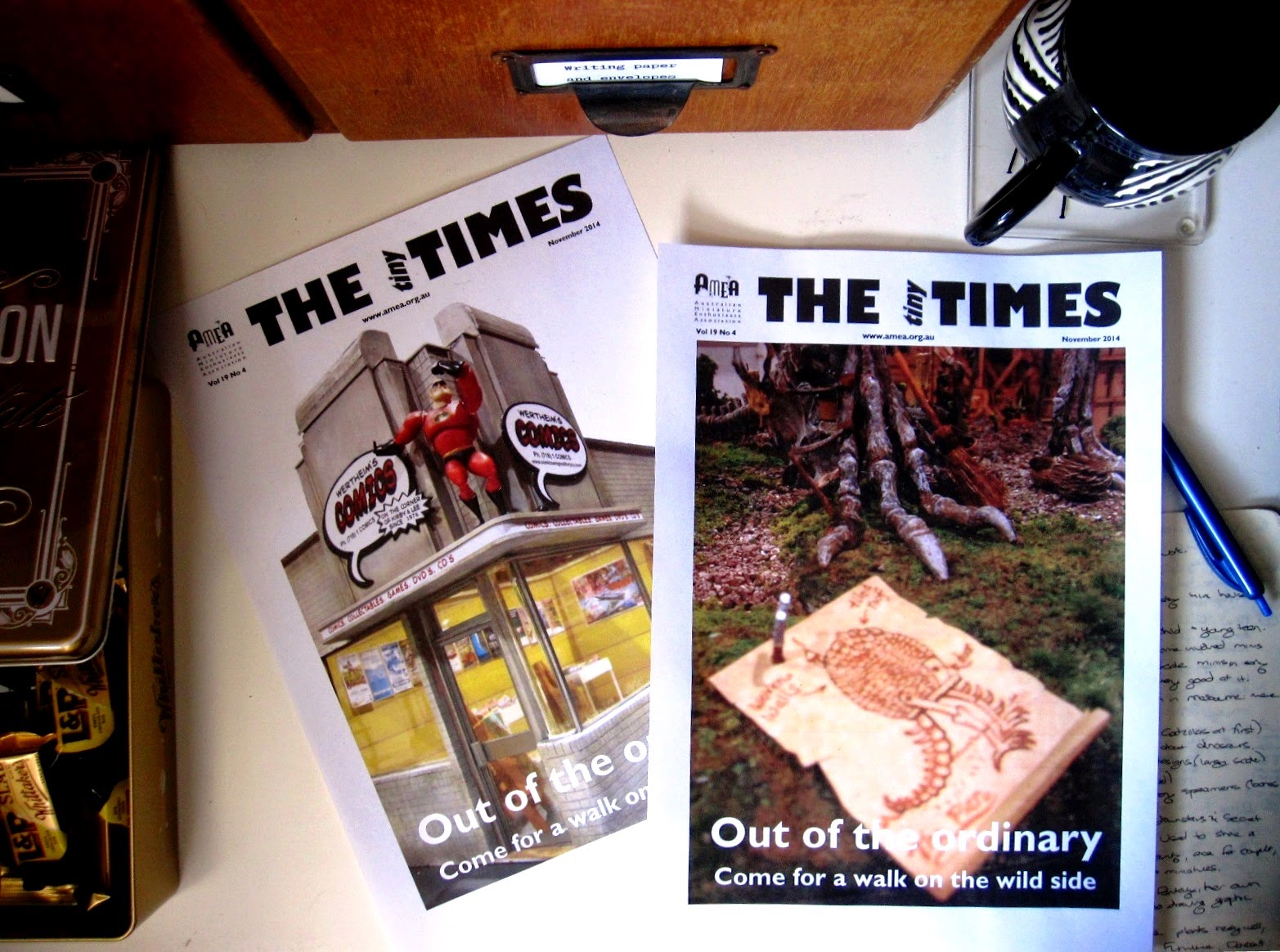 Desk with a tin of chocolate bars, two test covers for The tiny Times, a notebook and pen and an empty tea mug on it.