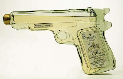 tequila in glass bottle shaped like handgun