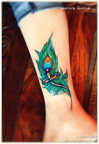 a peacock tattoo design on the ankle with bow shape pattern in the middle