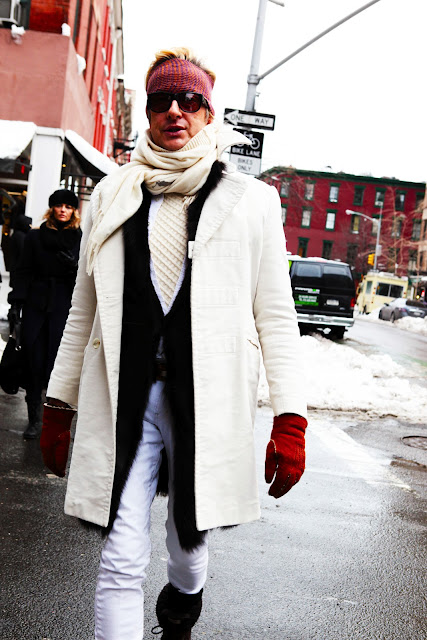 A very cold man wearing layer upon layer of apparently fashionable clothing.