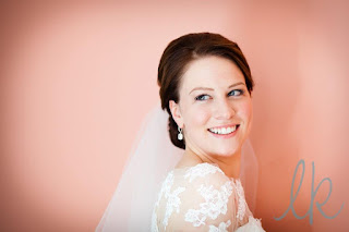 Smiling bride in front of a pink background