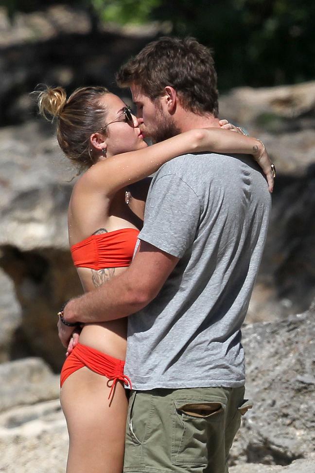 Miley Cyrus kissing Liam Hemsworth in an orange bikini
