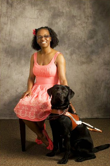 Tiffany wearing a pink dress poses with her guide dog Lando (black Lab in harness) at GDB graduation.