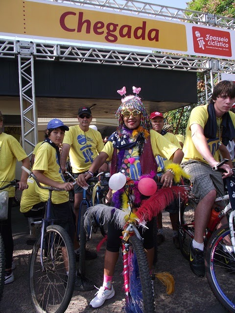 Ciclista fantasiada com uma peruca e um óculos amarelo em uma bicicleta decorada com balões