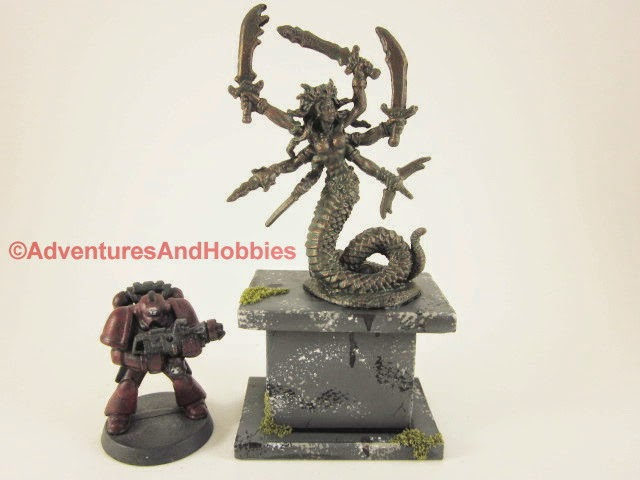 Miniature snake goddess of war statue with 28mm miniature for scale comparison.