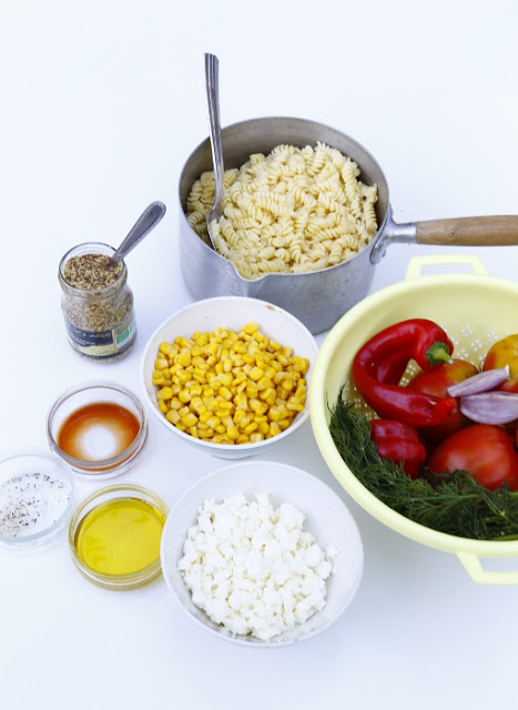 Bowls of various ingredients to make a pasta salad