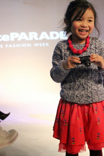 Chichi Mary | petitePARADE Fashion Show Fall 2015: Mary with camera in front of the runway.